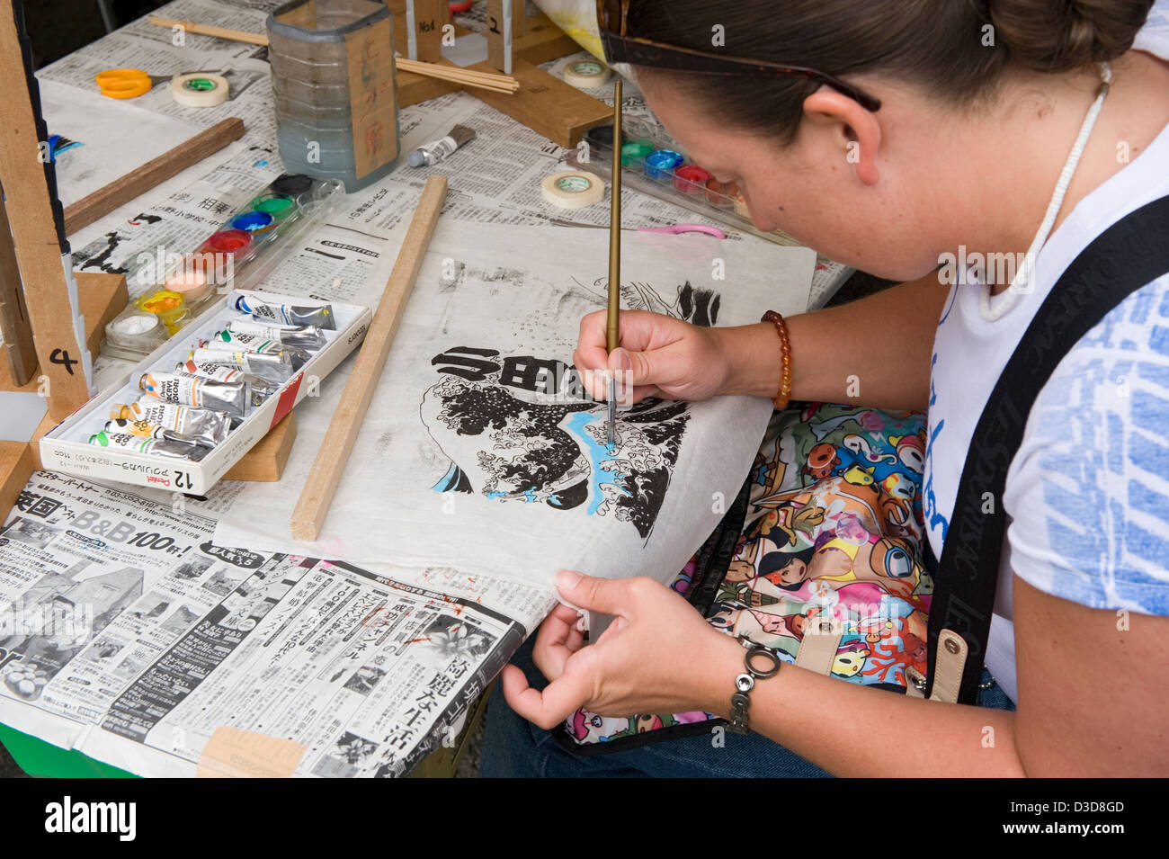 Non-Japanese female foreigner has a hand at painting a copy of old Ukiyo-e woodblock print at fair in Odawara, Kanagawa, - Stock Image