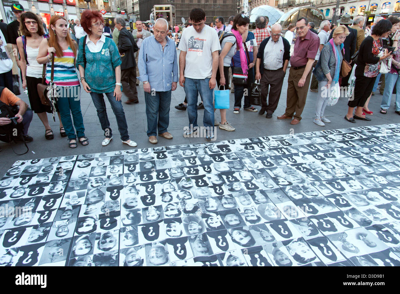 People looking at photos of victims of the Spanish Civil War in the Puerta del Sol, Madrid, Spain - Stock Image