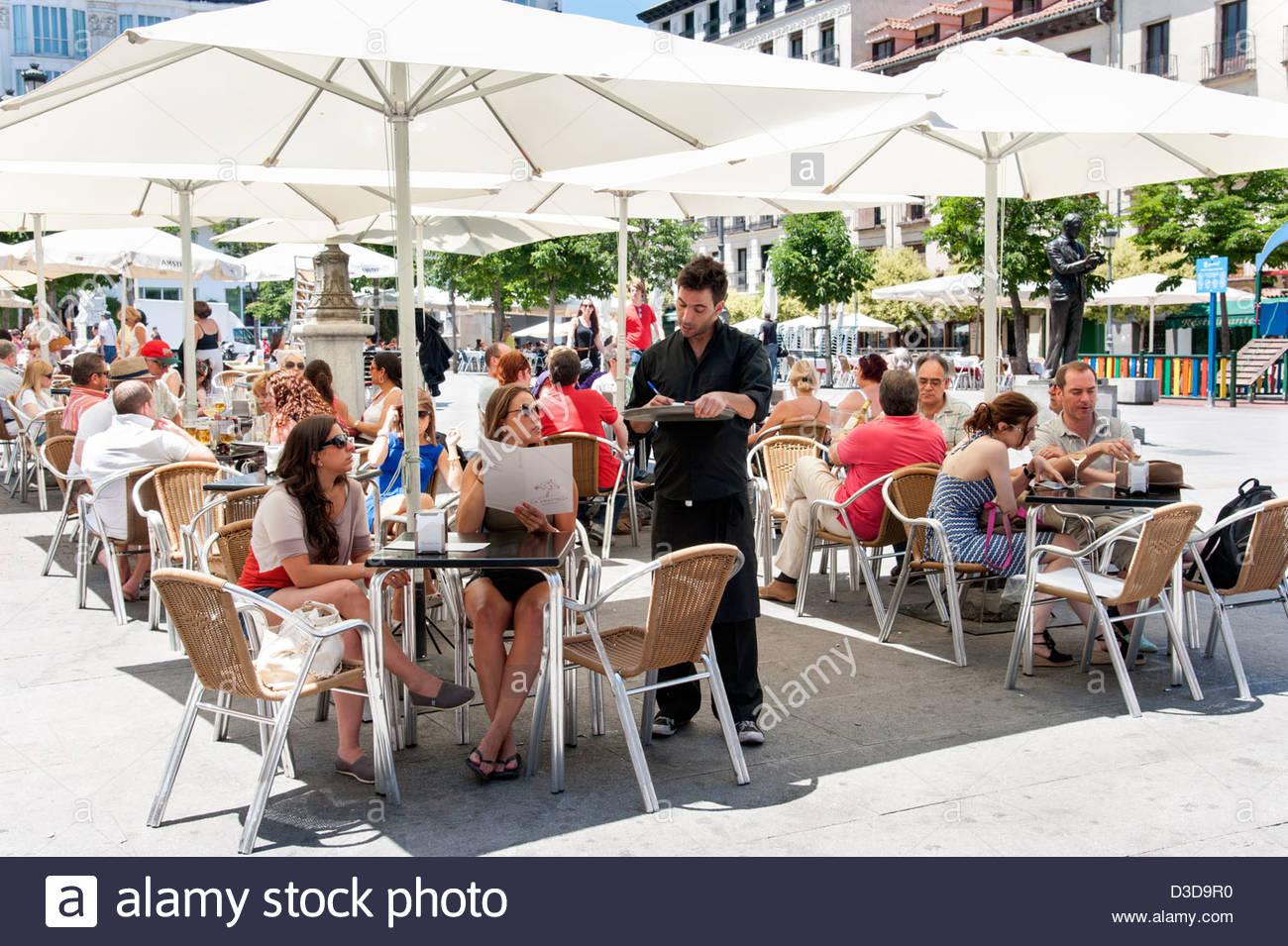 People ordering drinks at bar tables on Plaza de Santa Ana, Barrio de las Letras, Madrid, Spain - Stock Image
