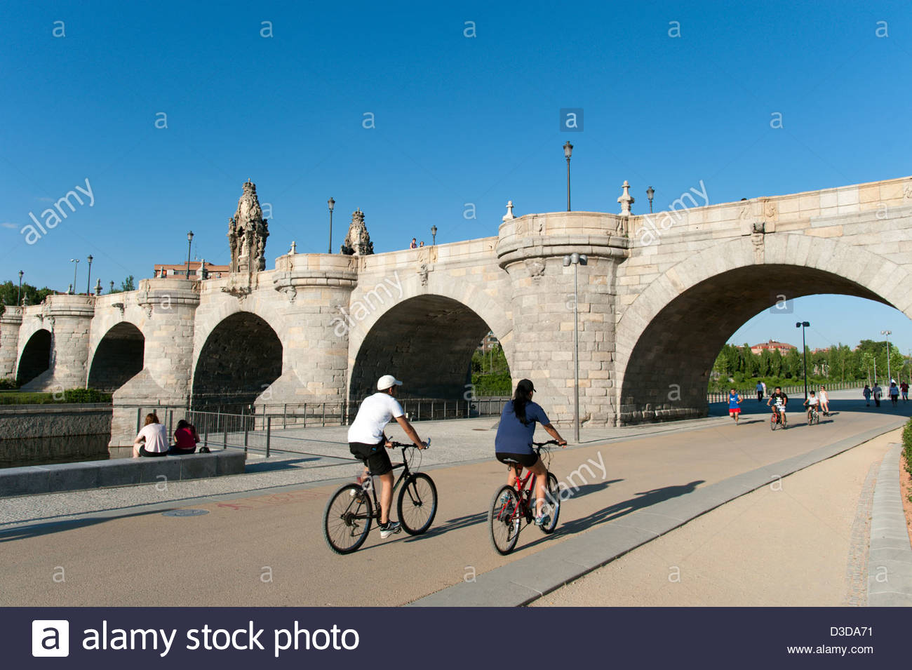 Cyclists on the Madrid Rio Park stretch of the Anillo Verde approaching the Puente de Toledo, Madrid, Spain - Stock Image