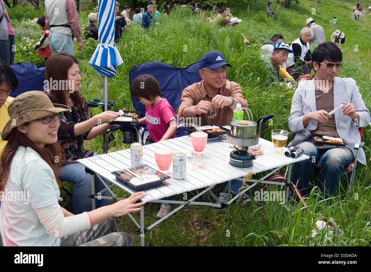 Outdoor family picnic Japanese style with fold-up table and chairs, camp stove and plenty of beer. - Stock Image