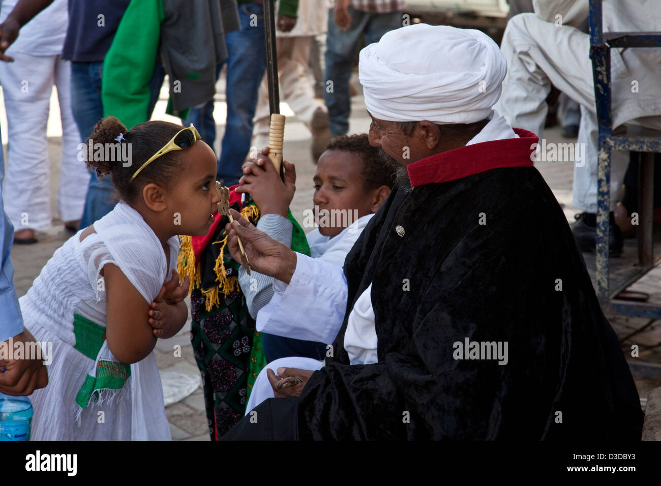 A Priest Blesses a Child In The Street During Timkat (The Festival of Epiphany), Gondar, Ethiopia - Stock Image