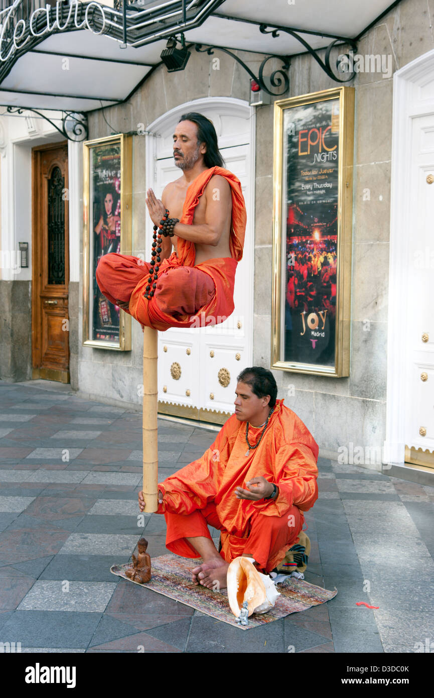Buddhist street entertainers performing a levitating illusion on Calle Arenal, Madrid, Spain - Stock Image