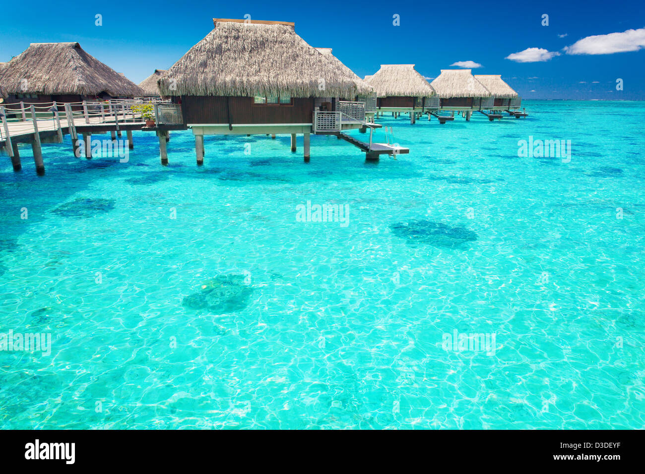 Water villas in the ocean with steps into turquoise lagoon - Stock Image