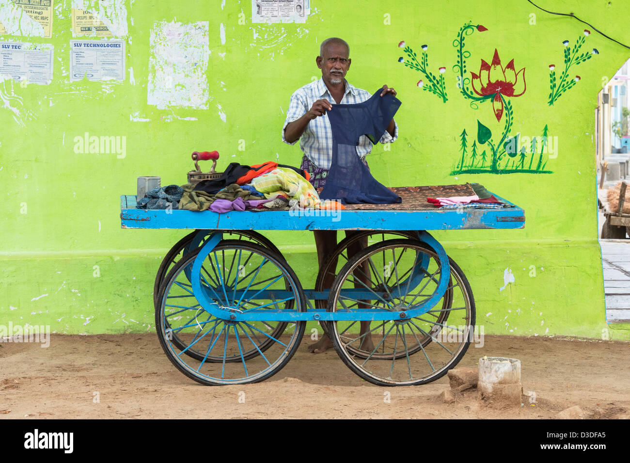 Traditional Indian street laundry man (dhobi) ironing washed clothes on a cart. Andhra Pradesh, India - Stock Image