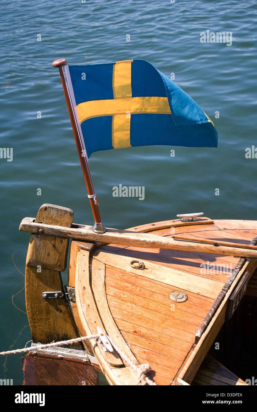 Hamburgsund, Sweden, a Swedish flag fluttering on a sailboat - Stock Image