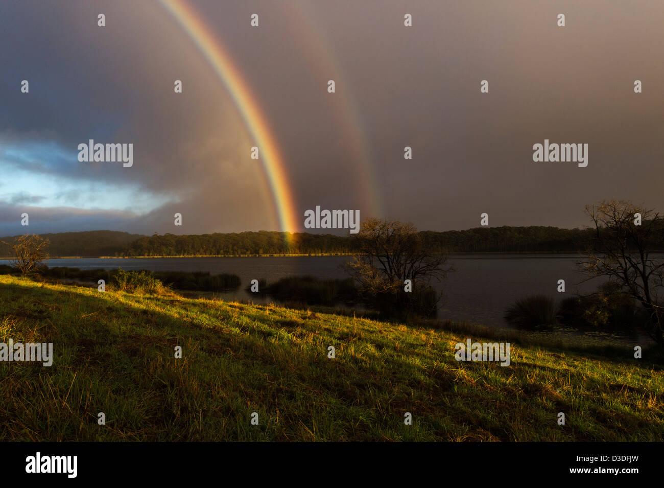 Rainbow over dam, QLD Australia - Stock Image