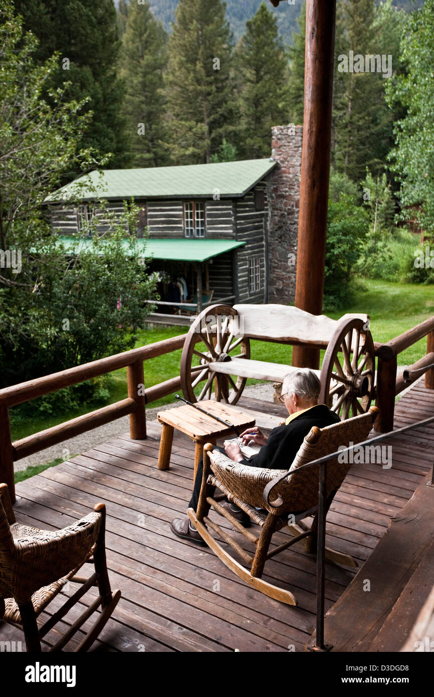 Elderly man sits in rocking chair on veranda of ranch in Montana, USA - Stock Image