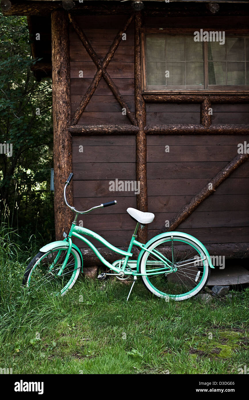 Childs bike parked on log cabin exterior in Montana, USA - Stock Image