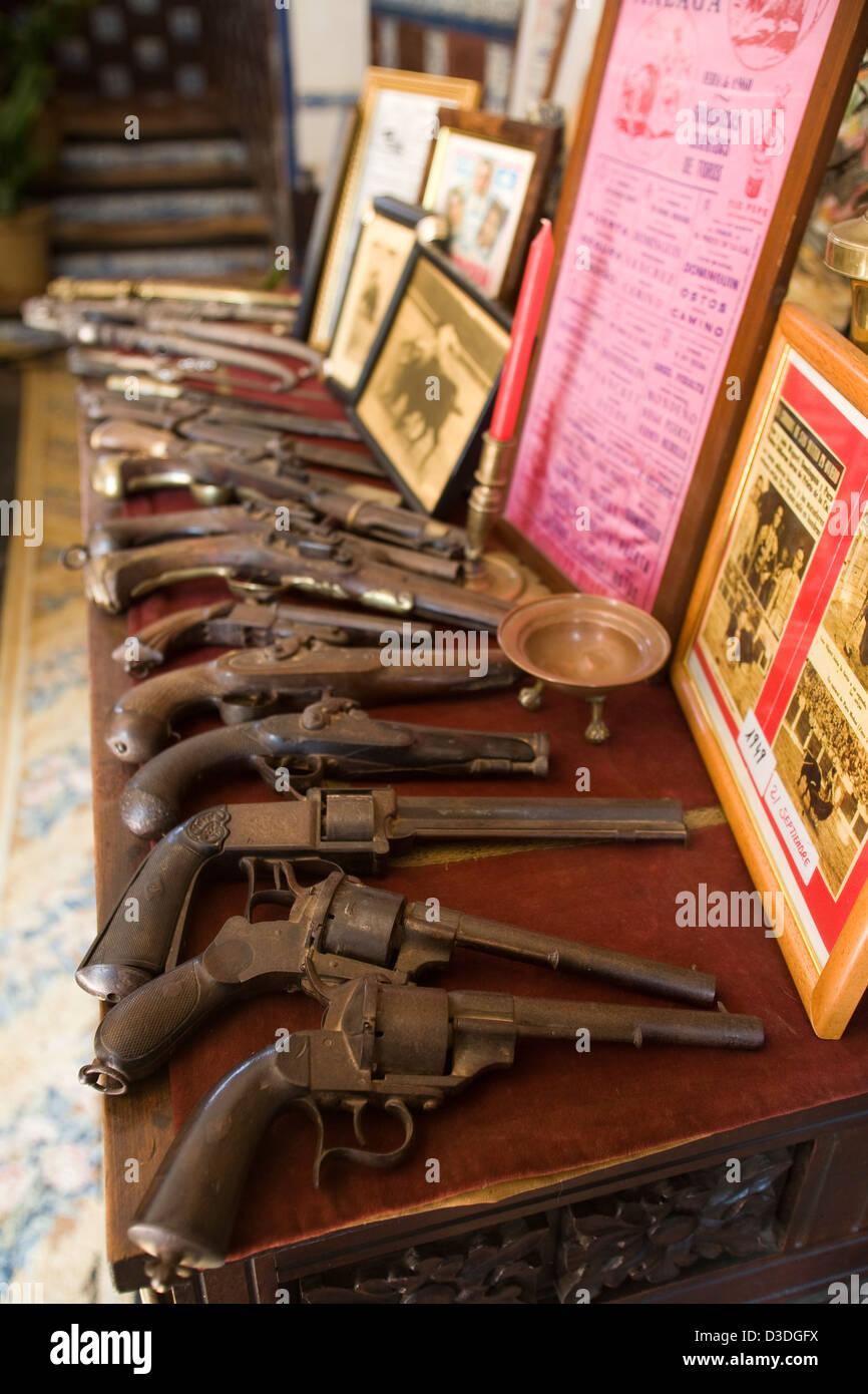 LA RUIZA FINCA, HUELVA, SPAIN, 21st FEBRUAY 2008: A collection of antique guns lie on a table beside bullfighting Stock Photo