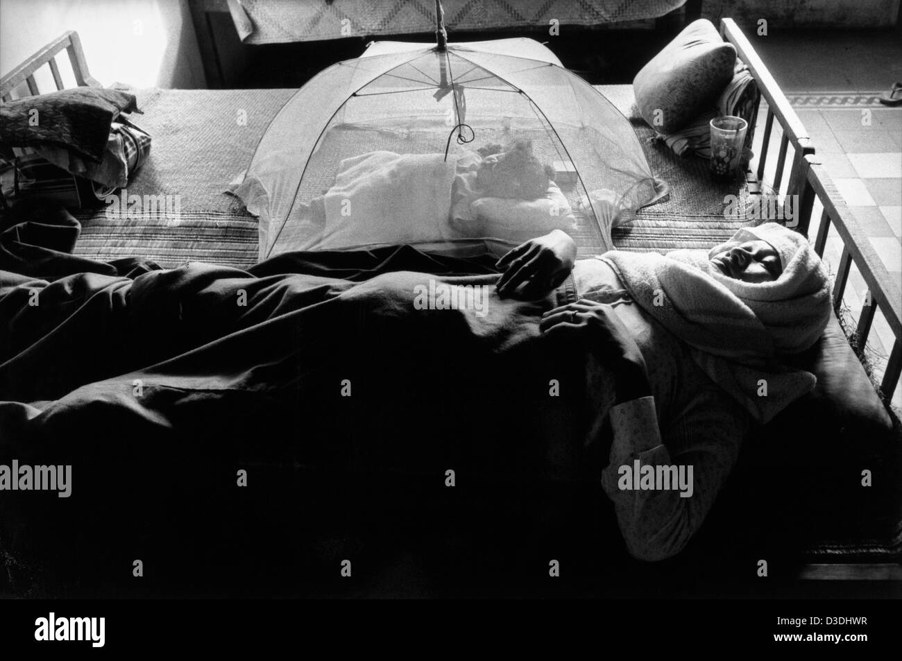 Takeo province, Cambodia: A mother recovers from giving birth while her baby daughter sleeps under a mosquito net, - Stock Image