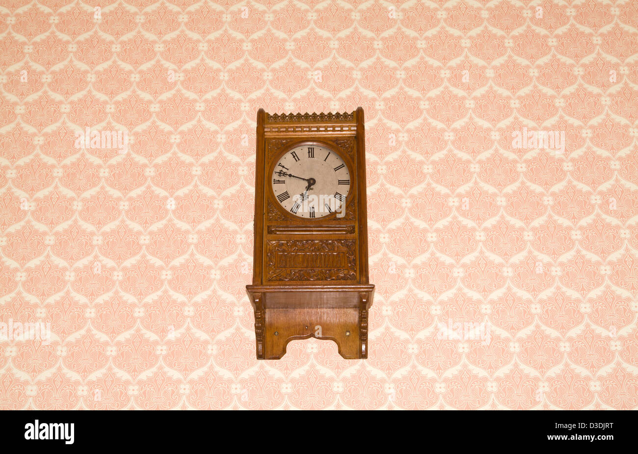 Wall clock on a wall with a designer wall paper - Stock Image