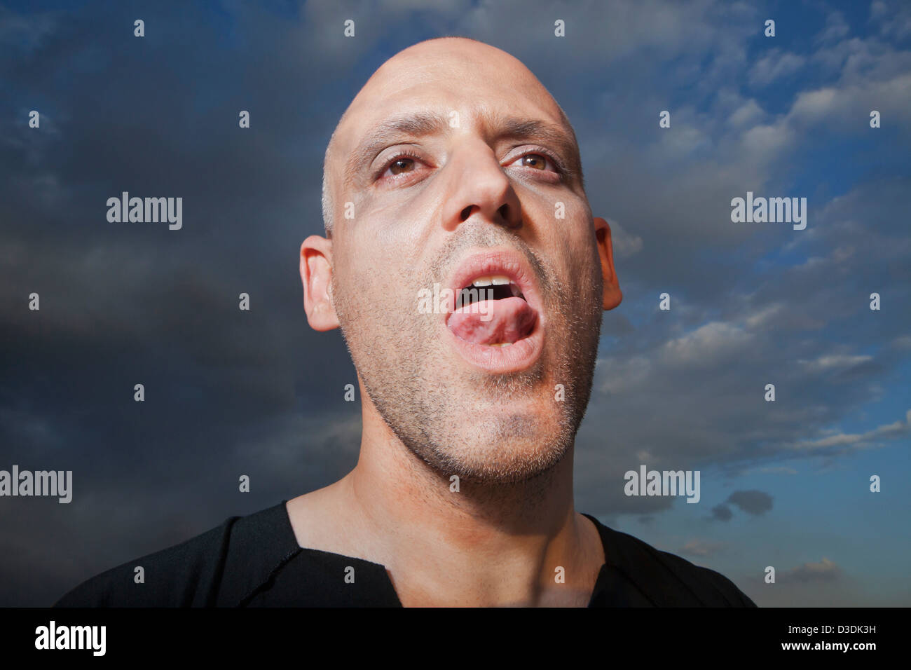 Close-up of a man sticking his tongue out - Stock Image