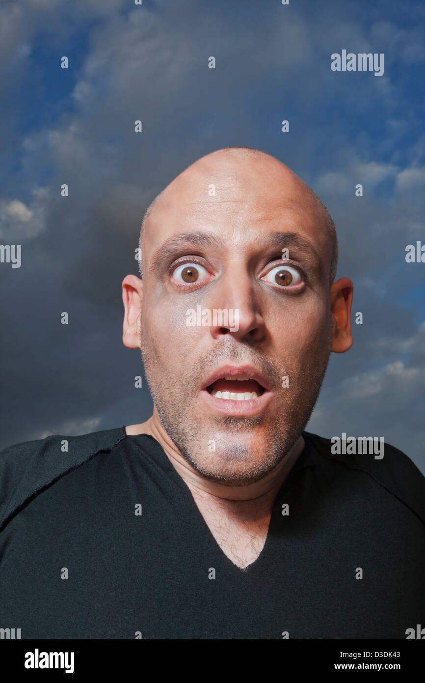 Man looking shocked in fear - Stock Image