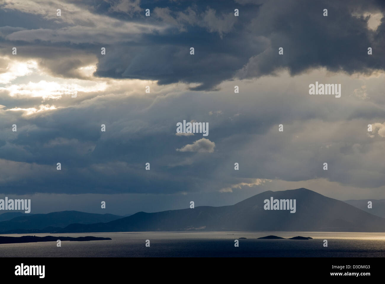 Dramatic sky above sea and mountains - Stock Image