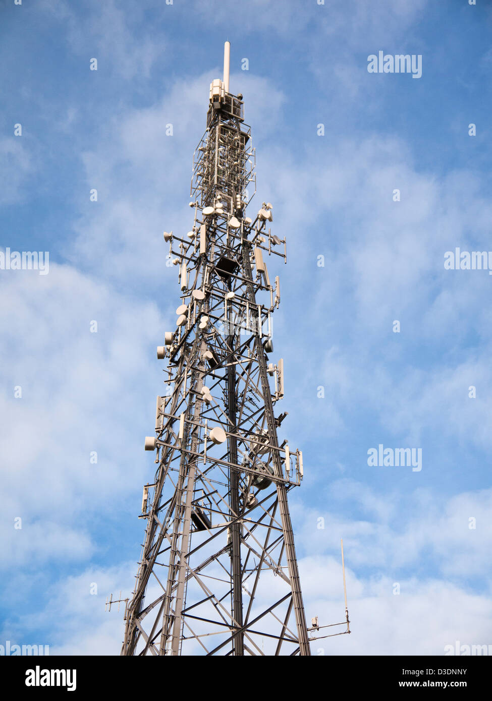 Communications tower with many aerials and dishes against a blue sky - Stock Image