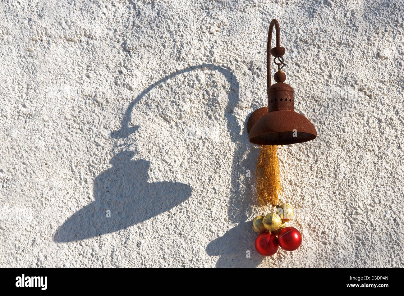 Rusty lamp with Christmas decoration and shadow on white exterior wall Stock Photo