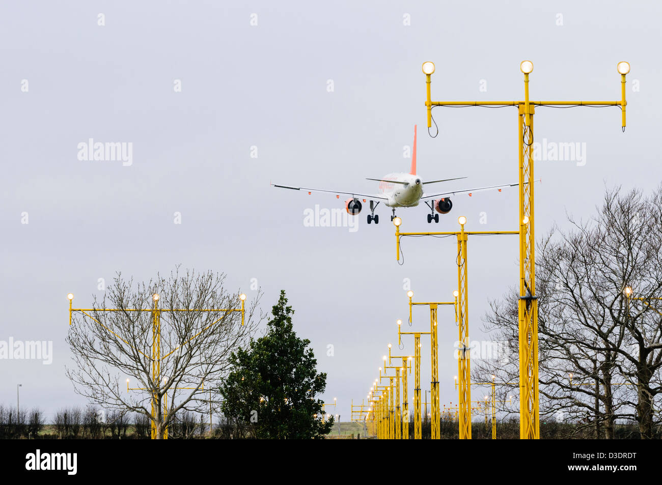 Easyjet plane flying over runway landing lights at an airport - Stock Image
