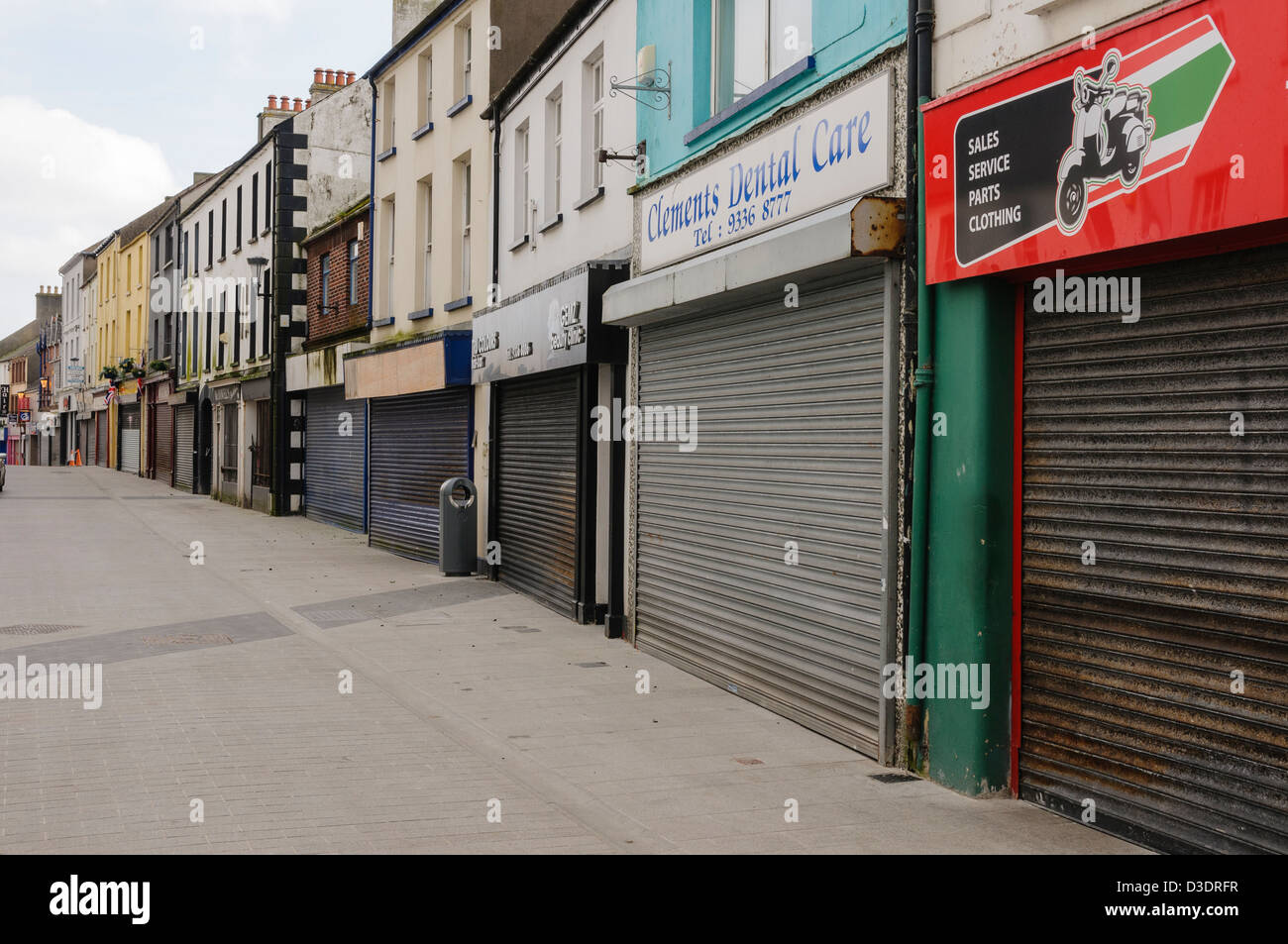 Street with shops all closed up and shuttered - Stock Image