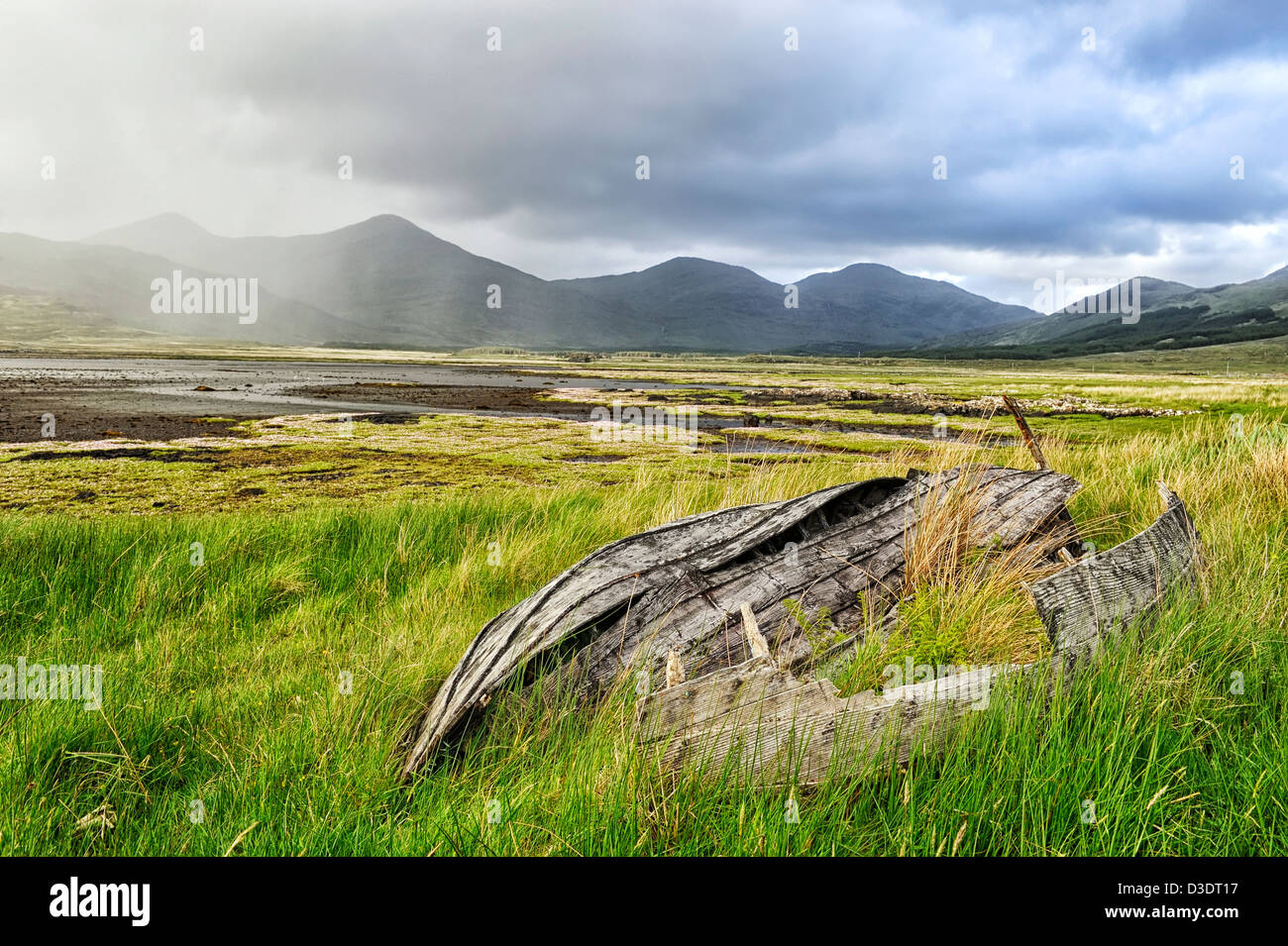 approaching storm & upturned old boat, mull, scotland - Stock Image