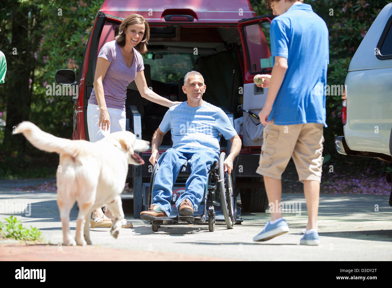 Man with spinal cord injury exiting an accessible van to see his family - Stock Image