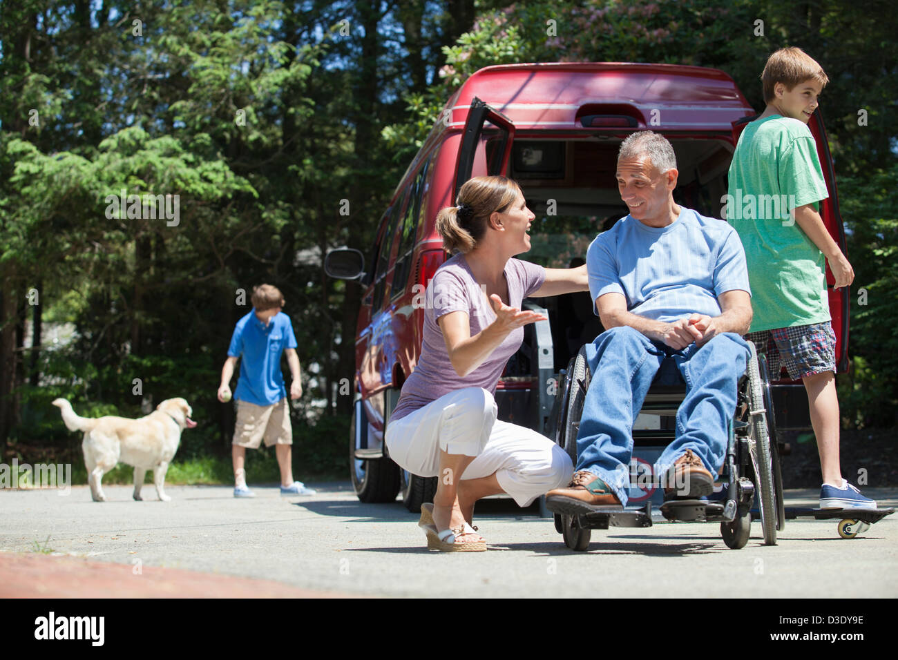 Man with spinal cord injury in wheelchair enjoying with his family - Stock Image