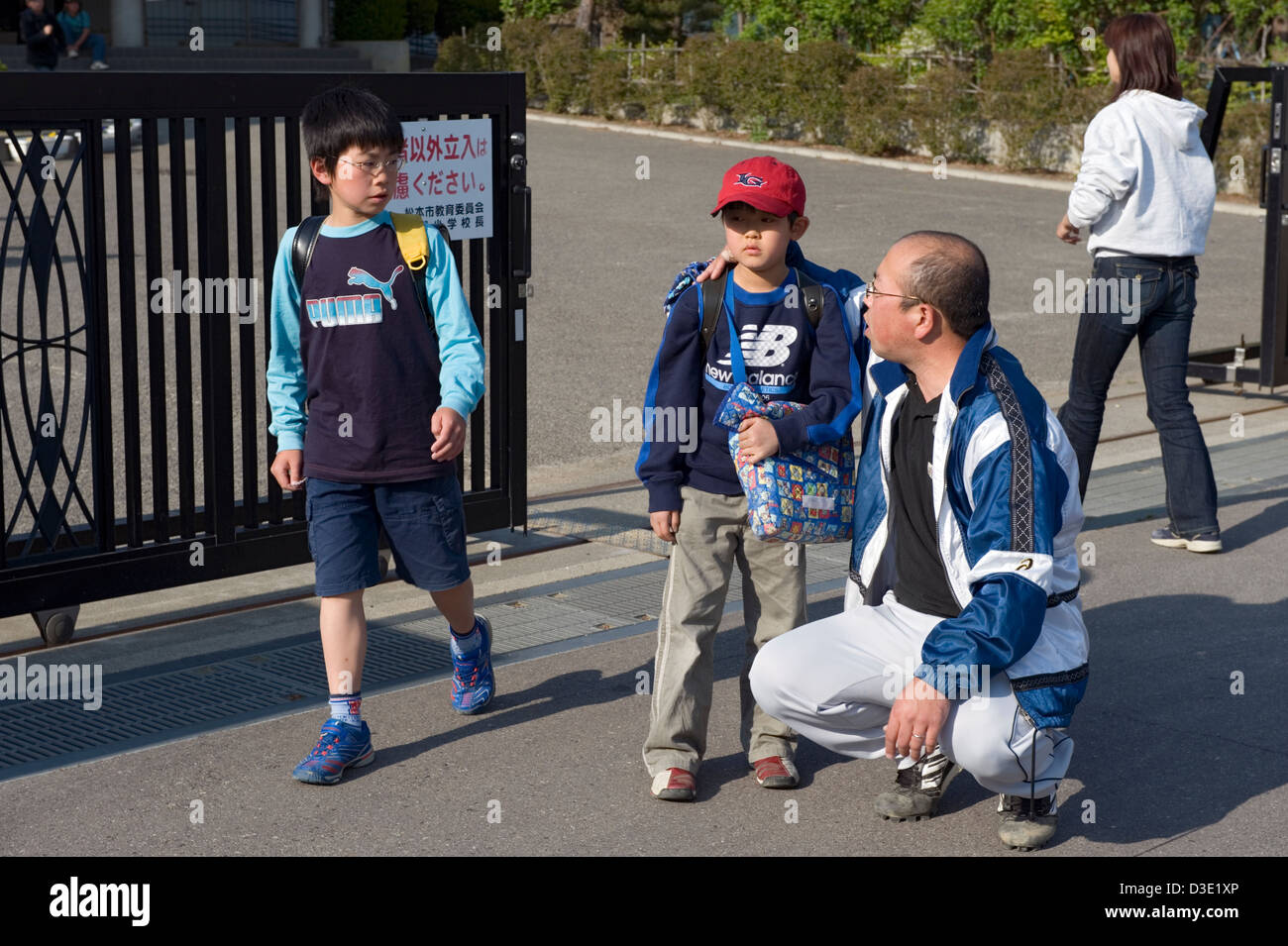In late afternoon a father picks his son up at a middle school in Matsumoto City, Nagano, Japan. - Stock Image