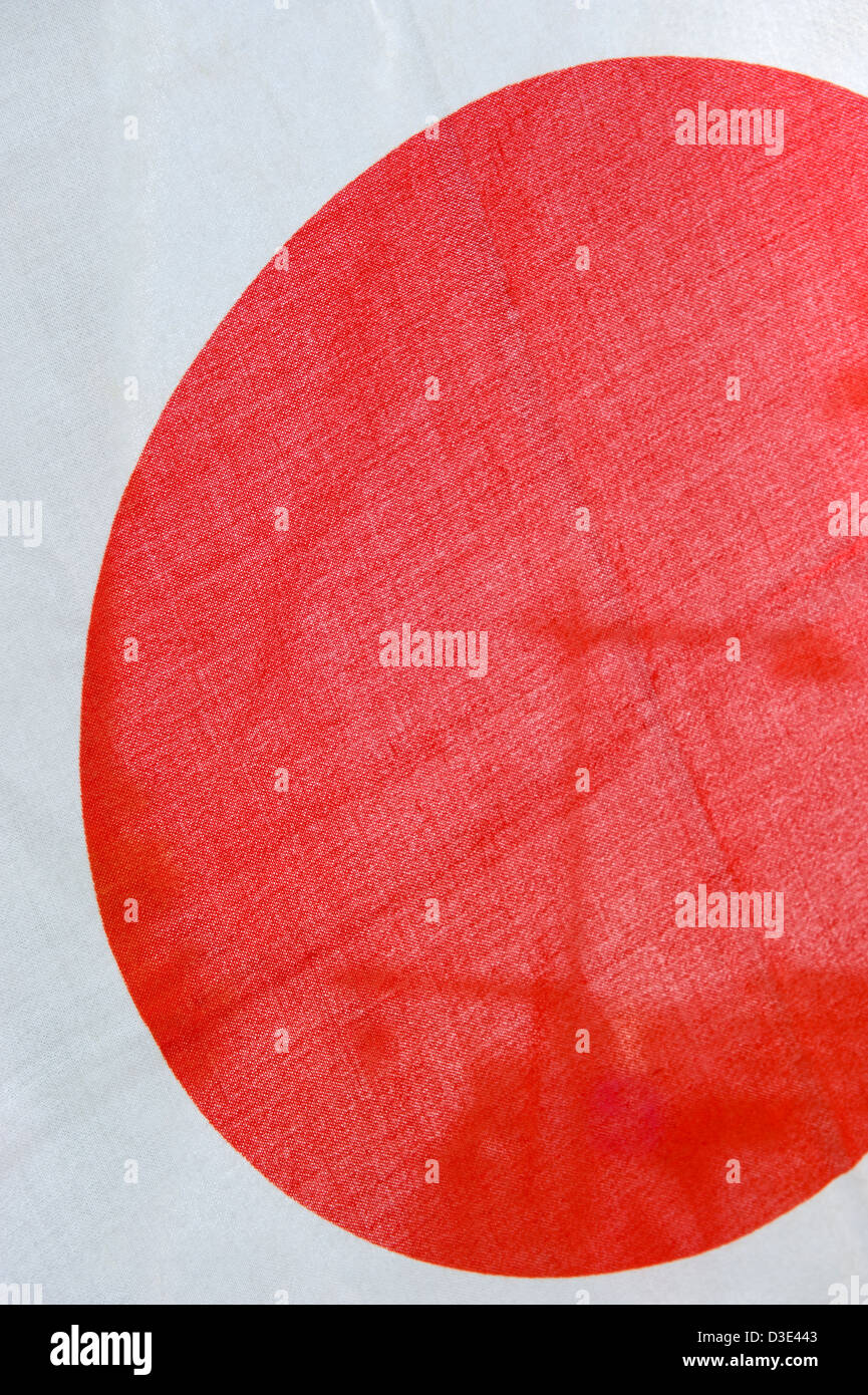 The Japanese flag is known as the hinomaru, or circle of the sun, or rising sun. A red disk against a white background. - Stock Image