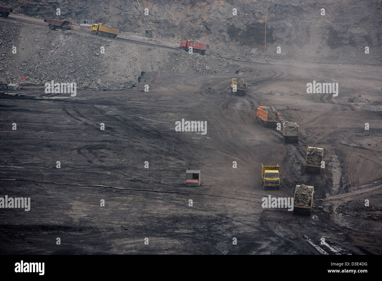 ORDOS, INNER MONGOLIA, CHINA - AUGUST 2007: A procession of 50 ton trucks are loaded with overburden on their way Stock Photo