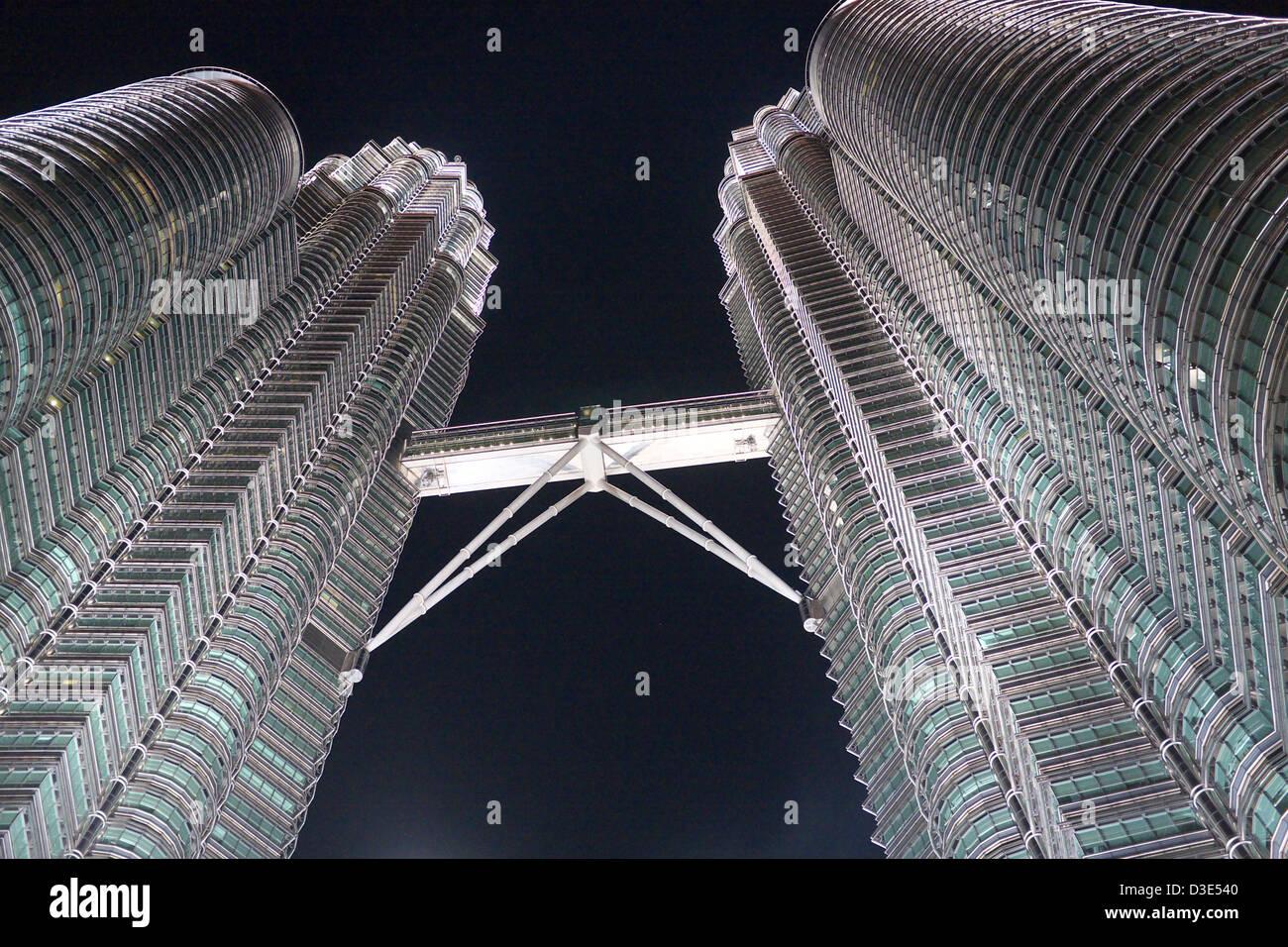 Petronas towers with pedestrian bridge between towers, at night - Stock Image