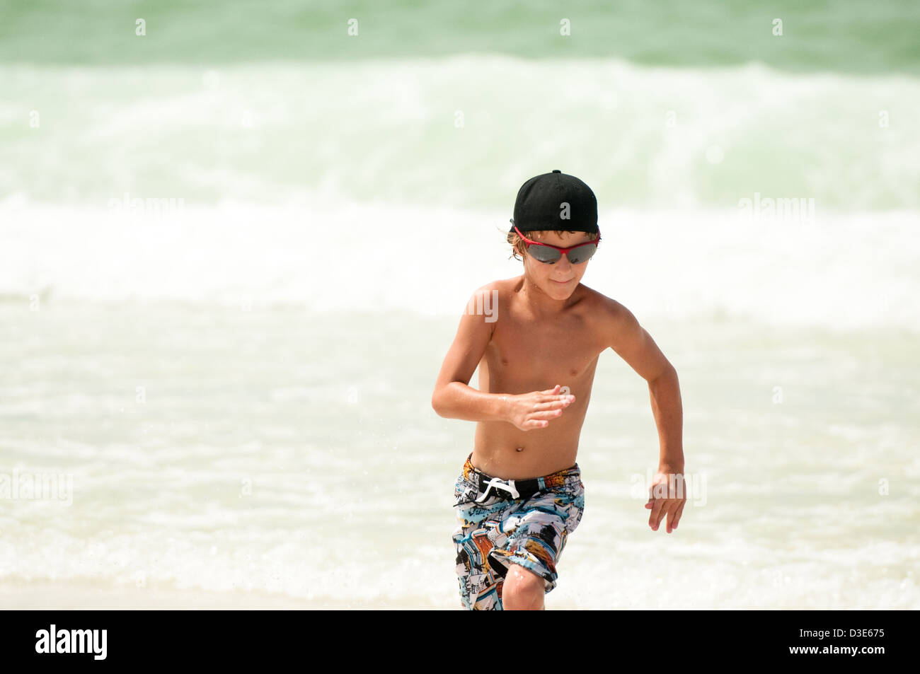 Young boy running through the ocean water on a beach wearing sunglasses and backwards hat. Stock Photo
