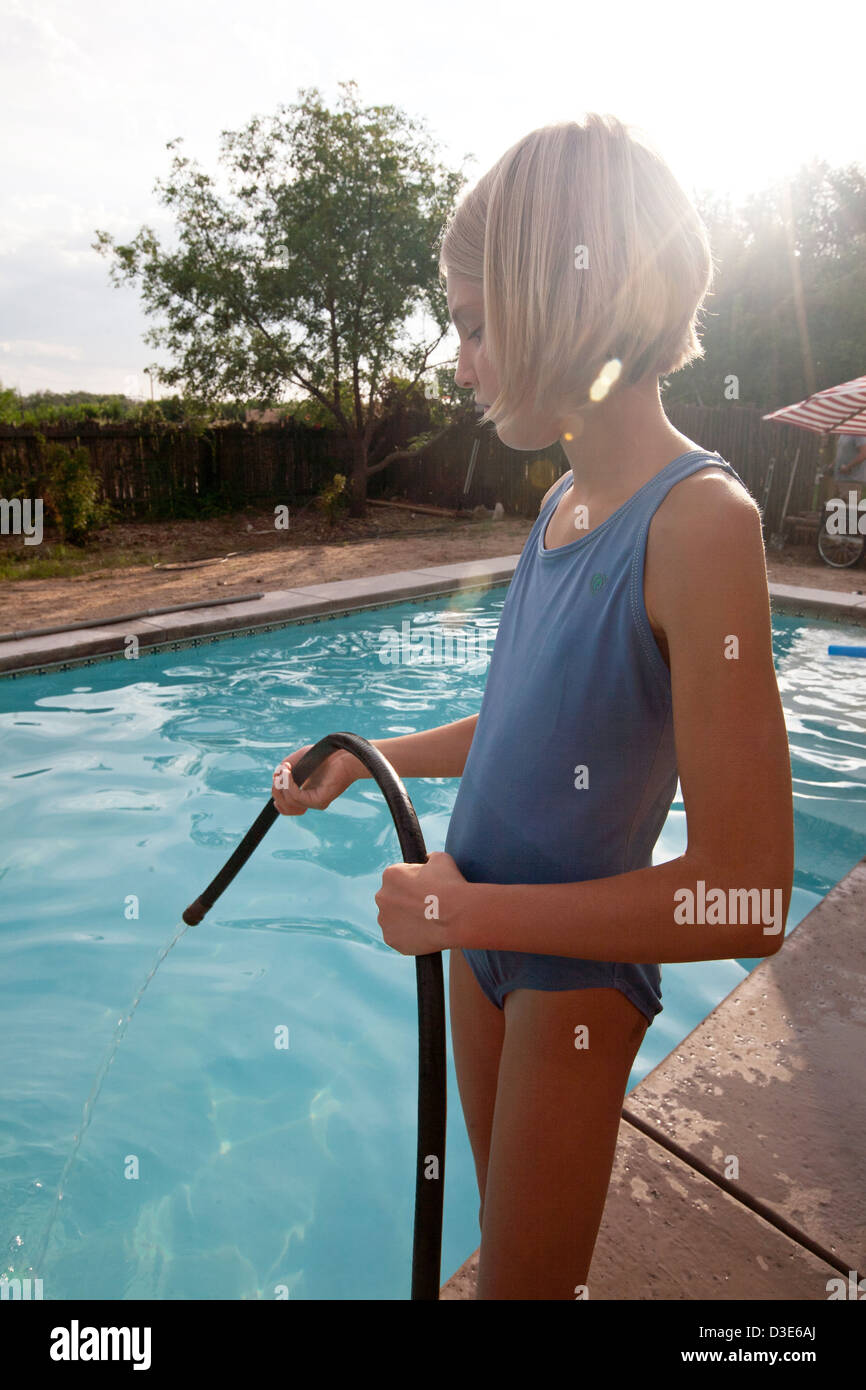 Ten year old girl pouring water into a swimming pool from a hose. Stock Photo
