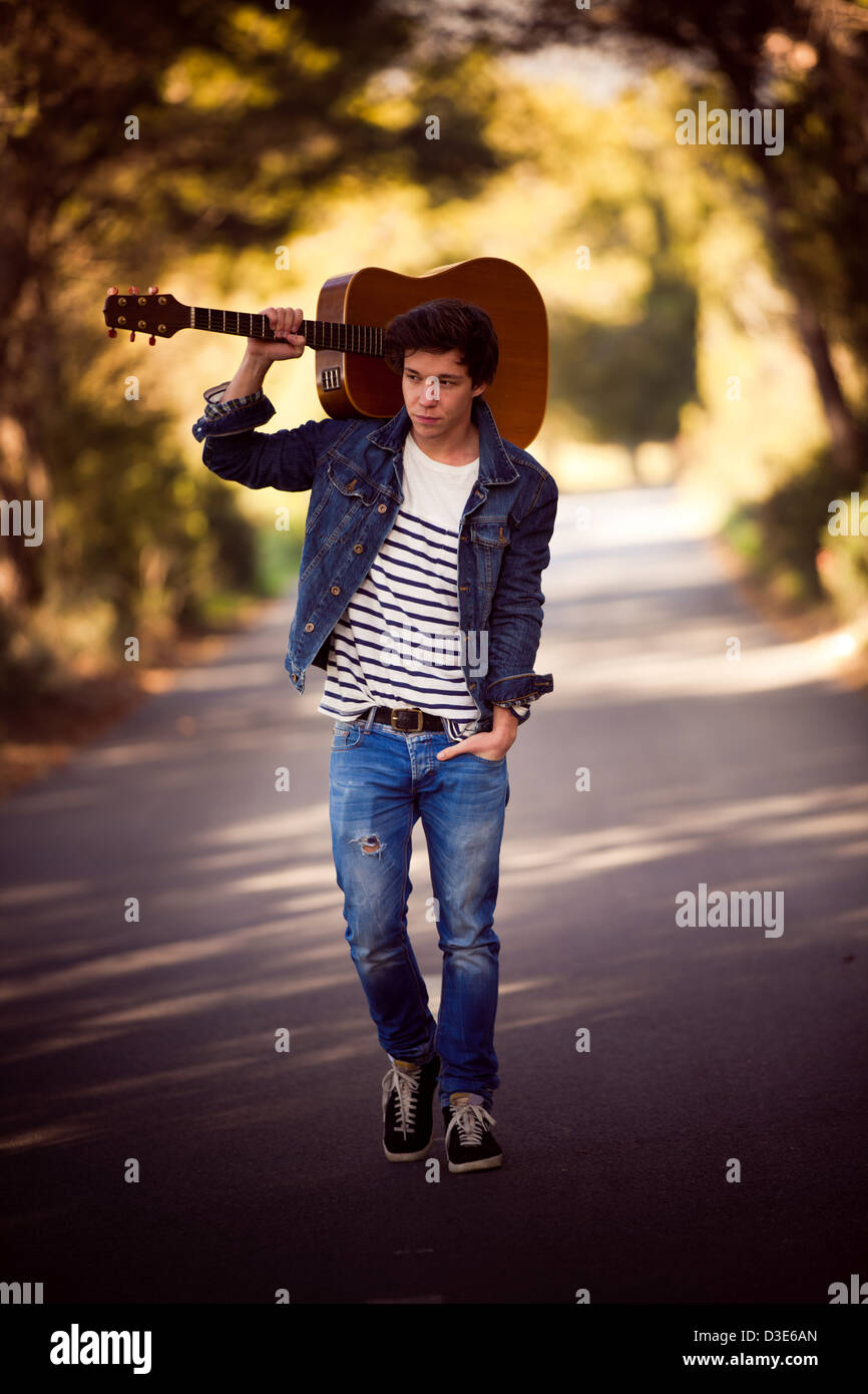 drifter, man with guitar walking outdoors - Stock Image