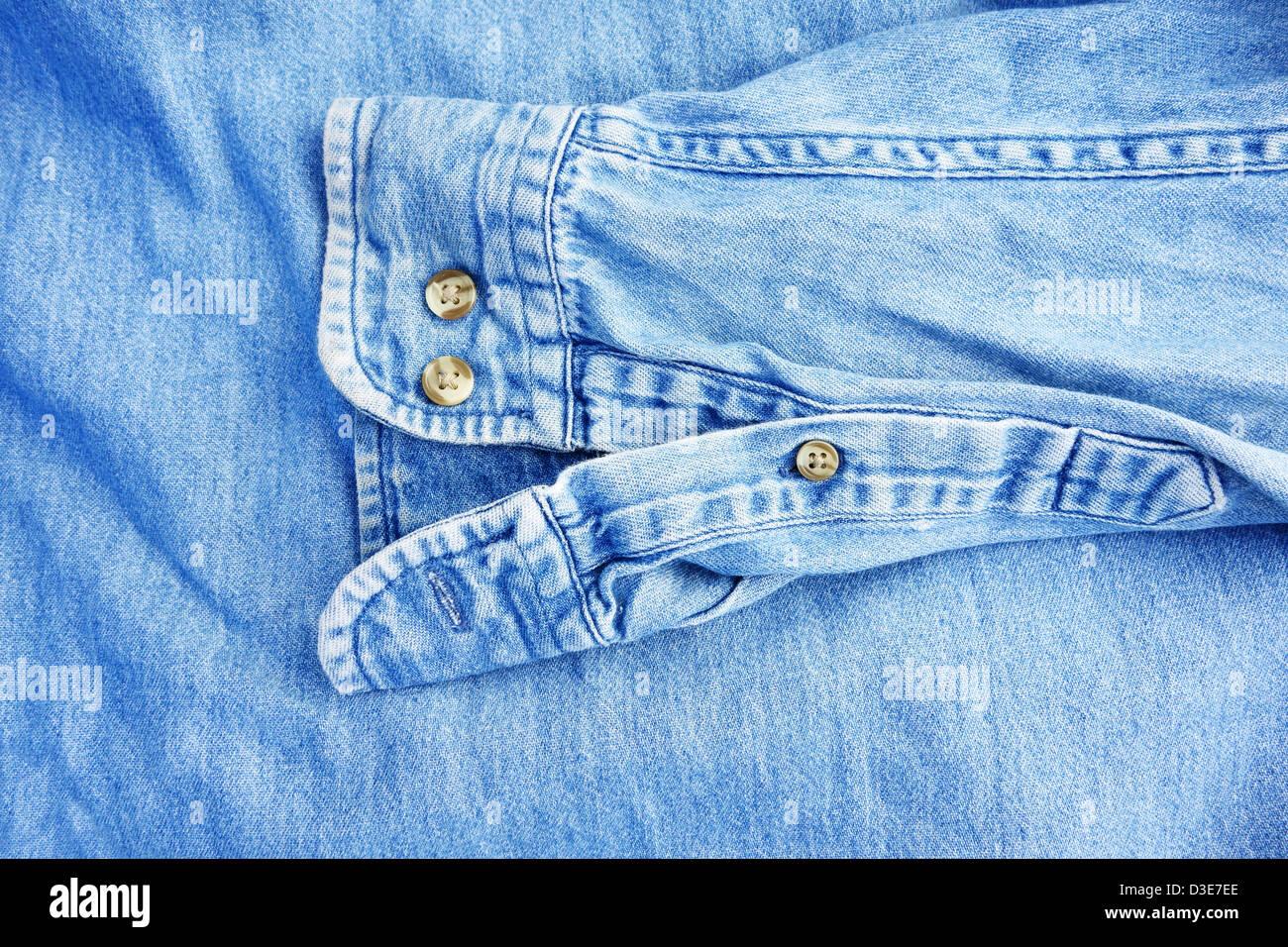 Denim shirt sleeve on top of denim material - Stock Image