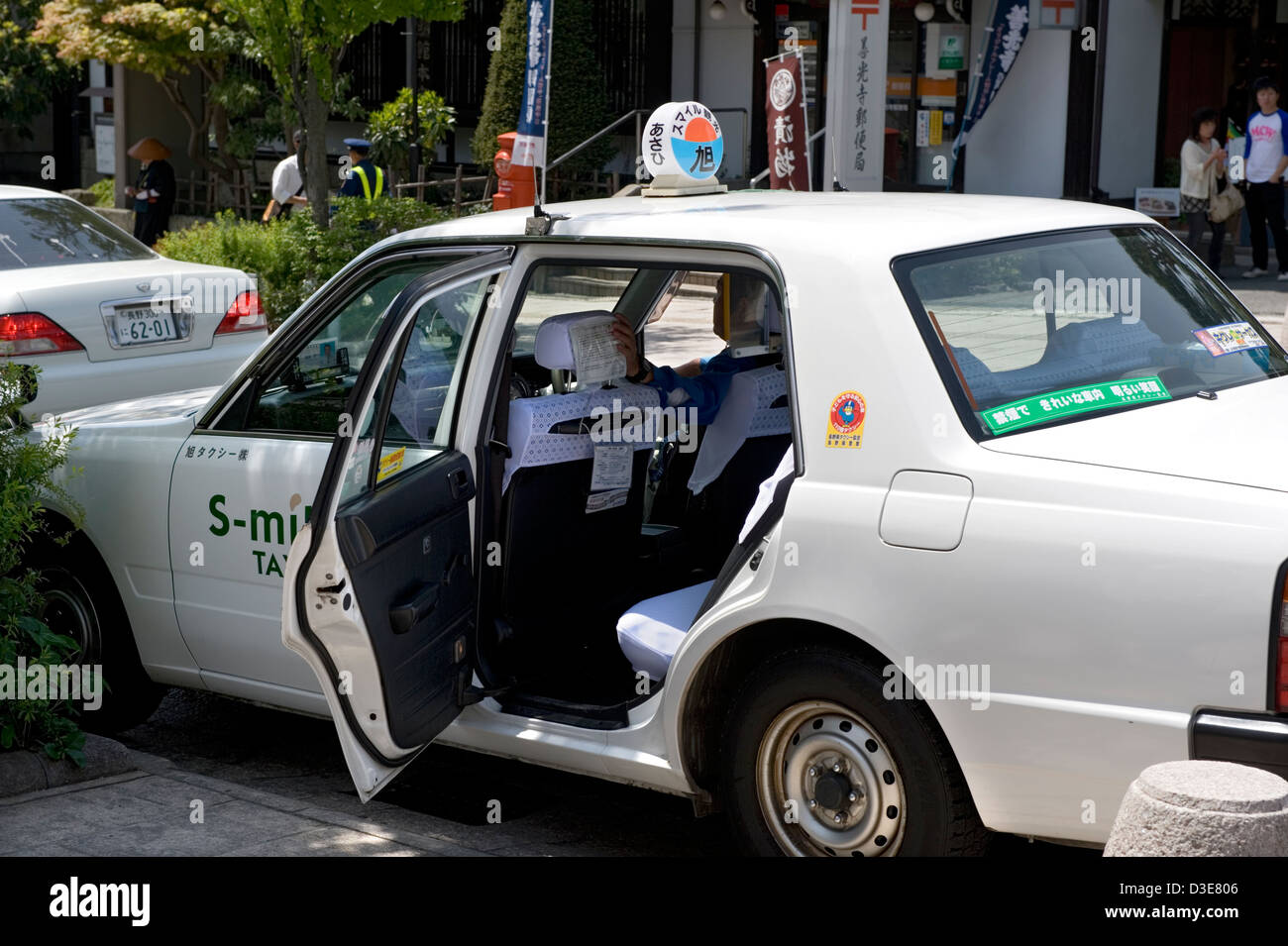 Japanese taxi cab waiting for passenger with right-rear door open. Clean, efficient, honest and comfort of white Stock Photo