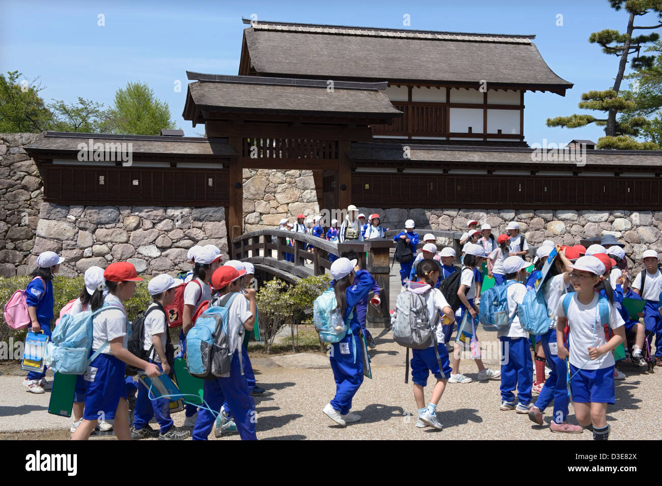 Elementary school children on outing crossing historic moat bridge at Kita-Akazumon gate at Matsushiro Castle in - Stock Image