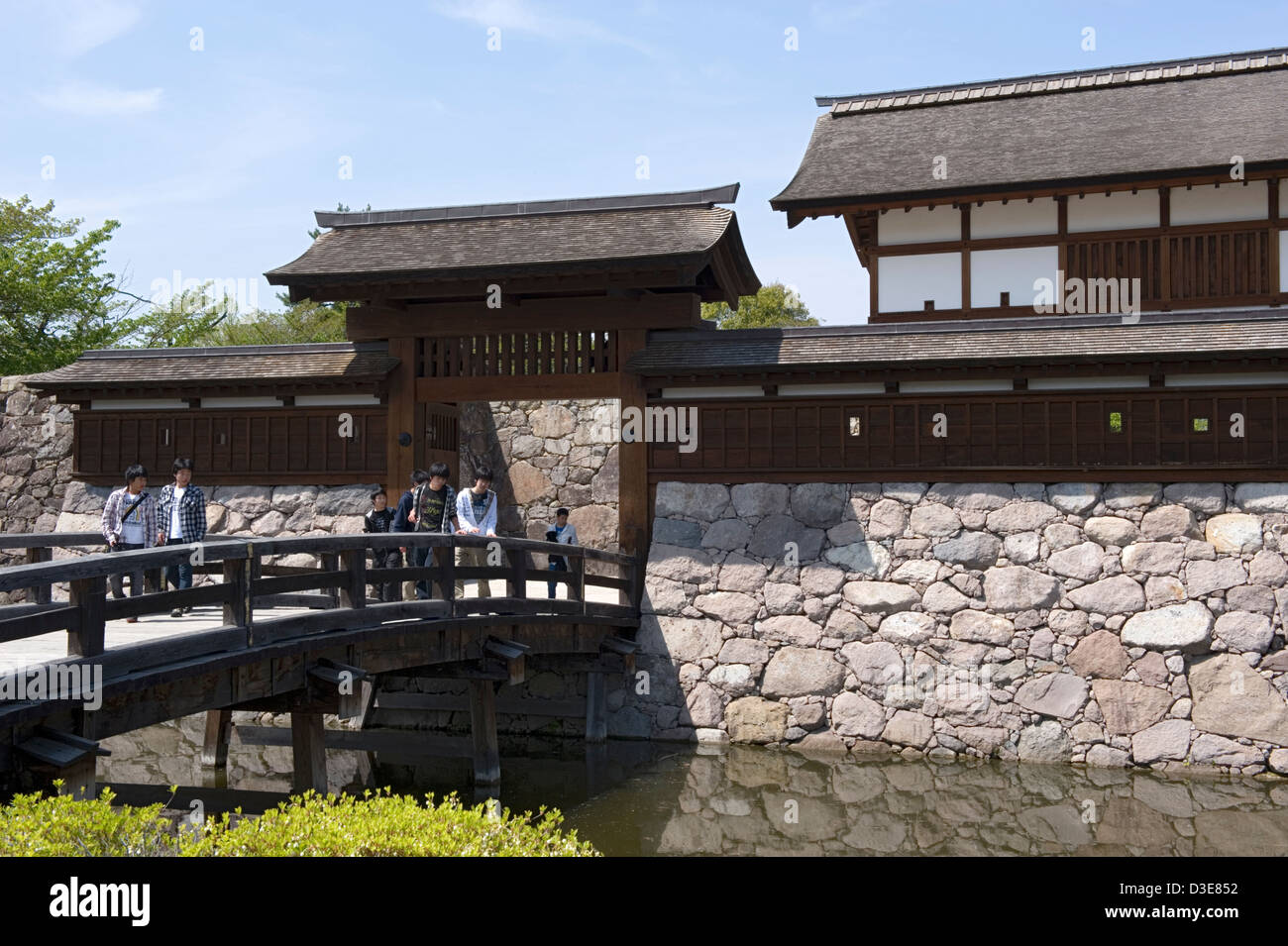 Young visitors crossing wooden bridge over moat and Kita-Akazumon covered gate at historic Matsushiro Castle in - Stock Image