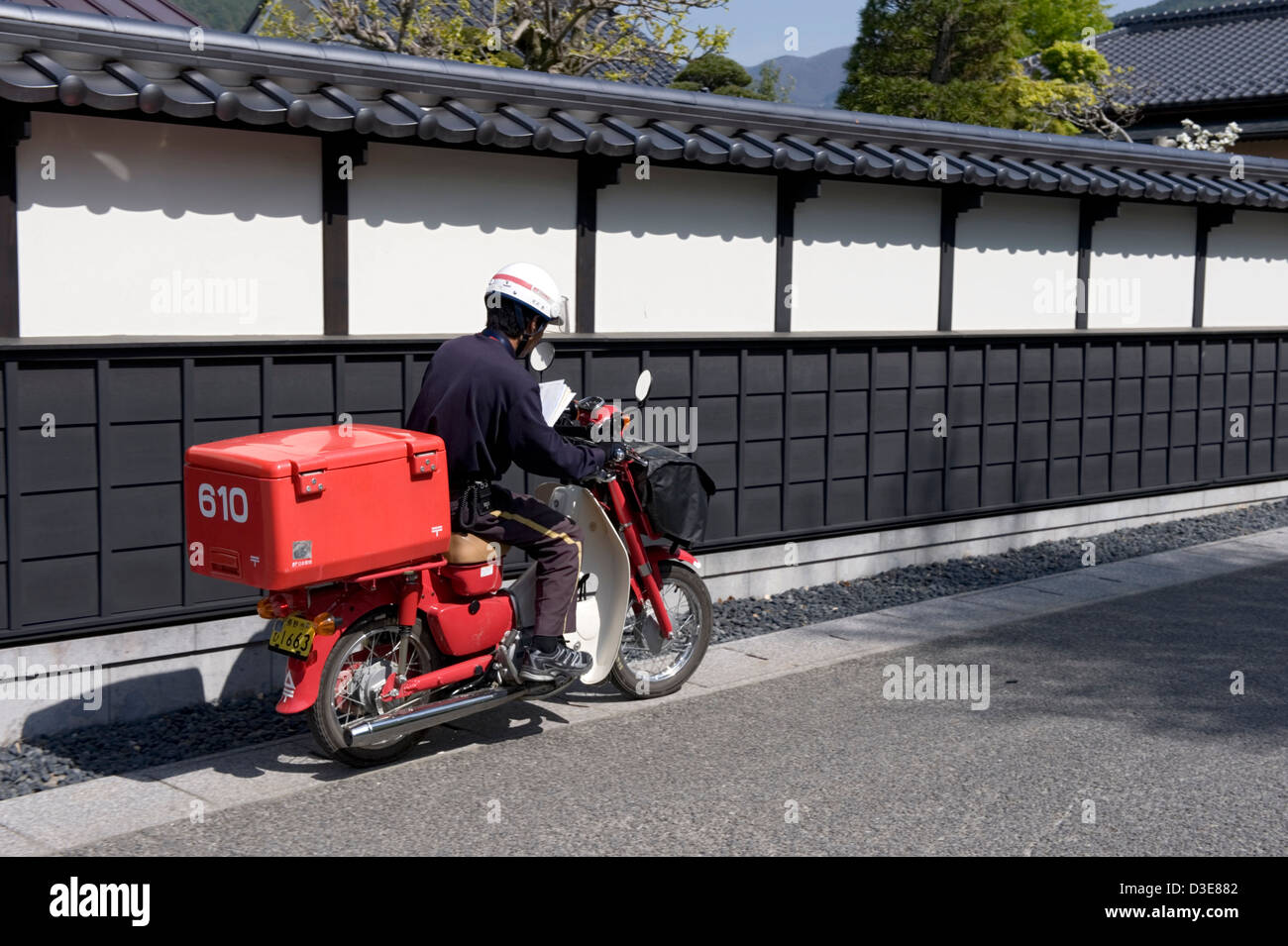 A typical red motor scooter used by the Japanese Postal System to deliver mail all around the country. - Stock Image