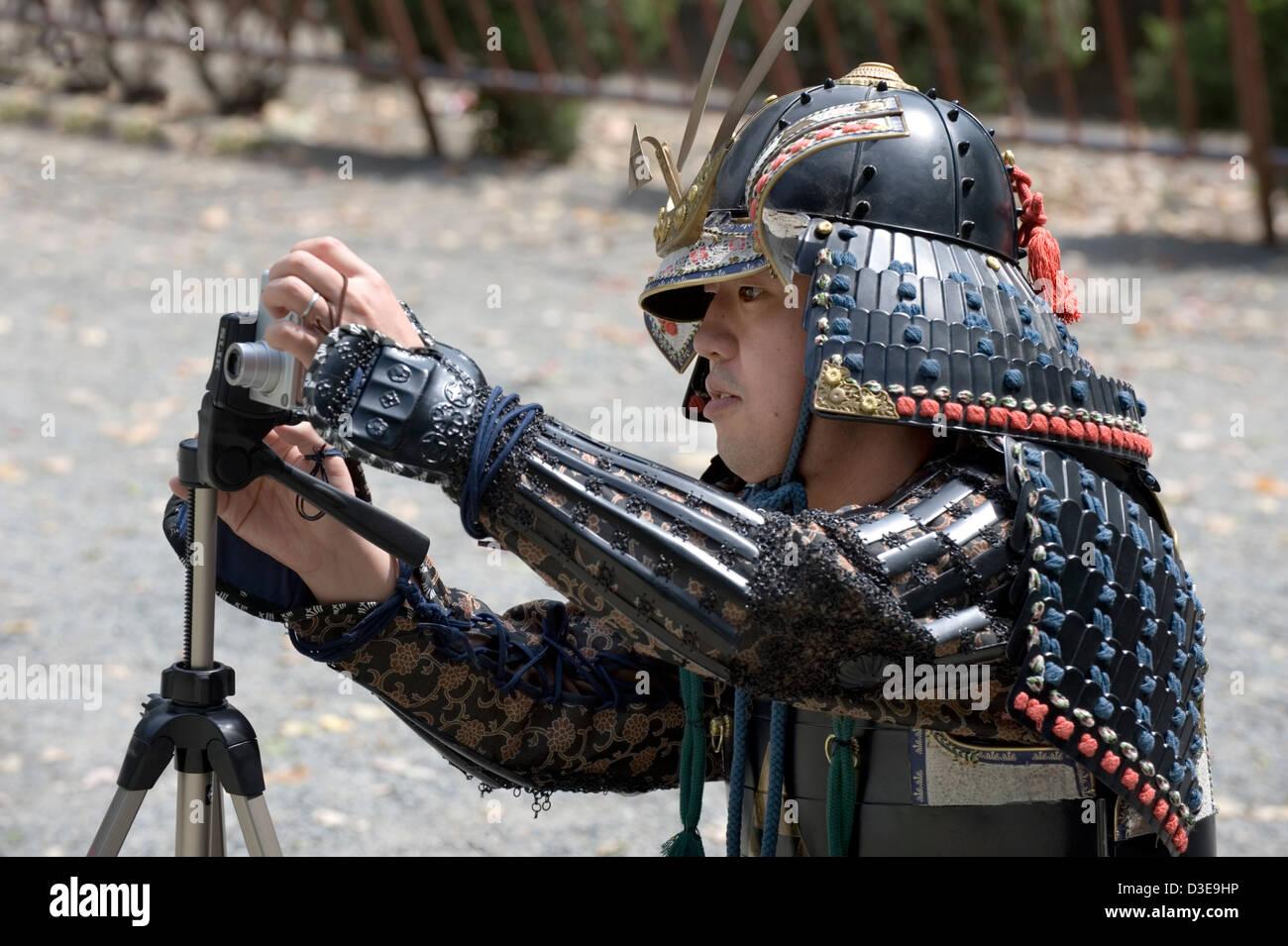 A young Sunday samurai sets up his camera for a commemorative shot during a festival at Odawara Castle in Kanagawa - Stock Image