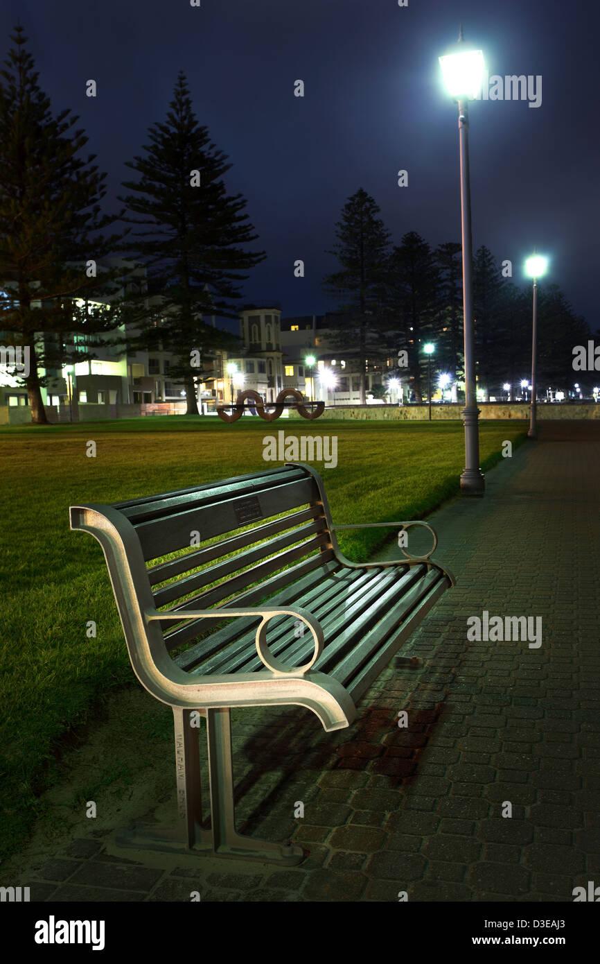 Empty park bench on the foreshore at Glenelg, South Australia. - Stock Image
