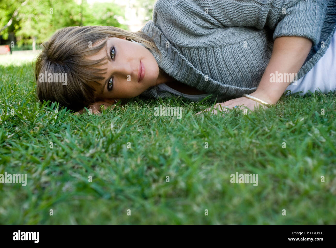 Woman lying in park - Stock Image