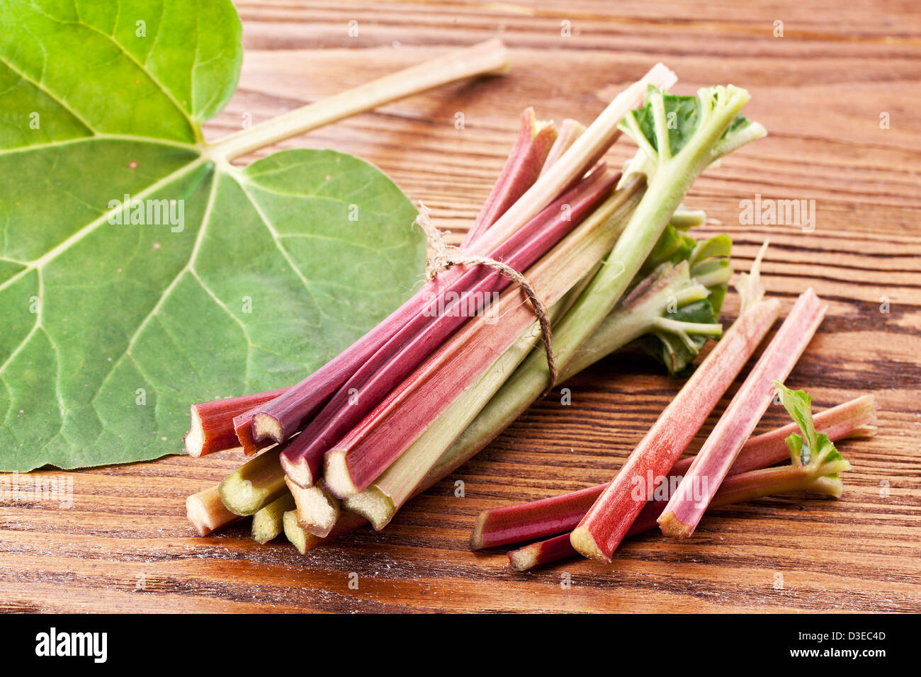 Rhubarb stalks on a wooden table. - Stock Image