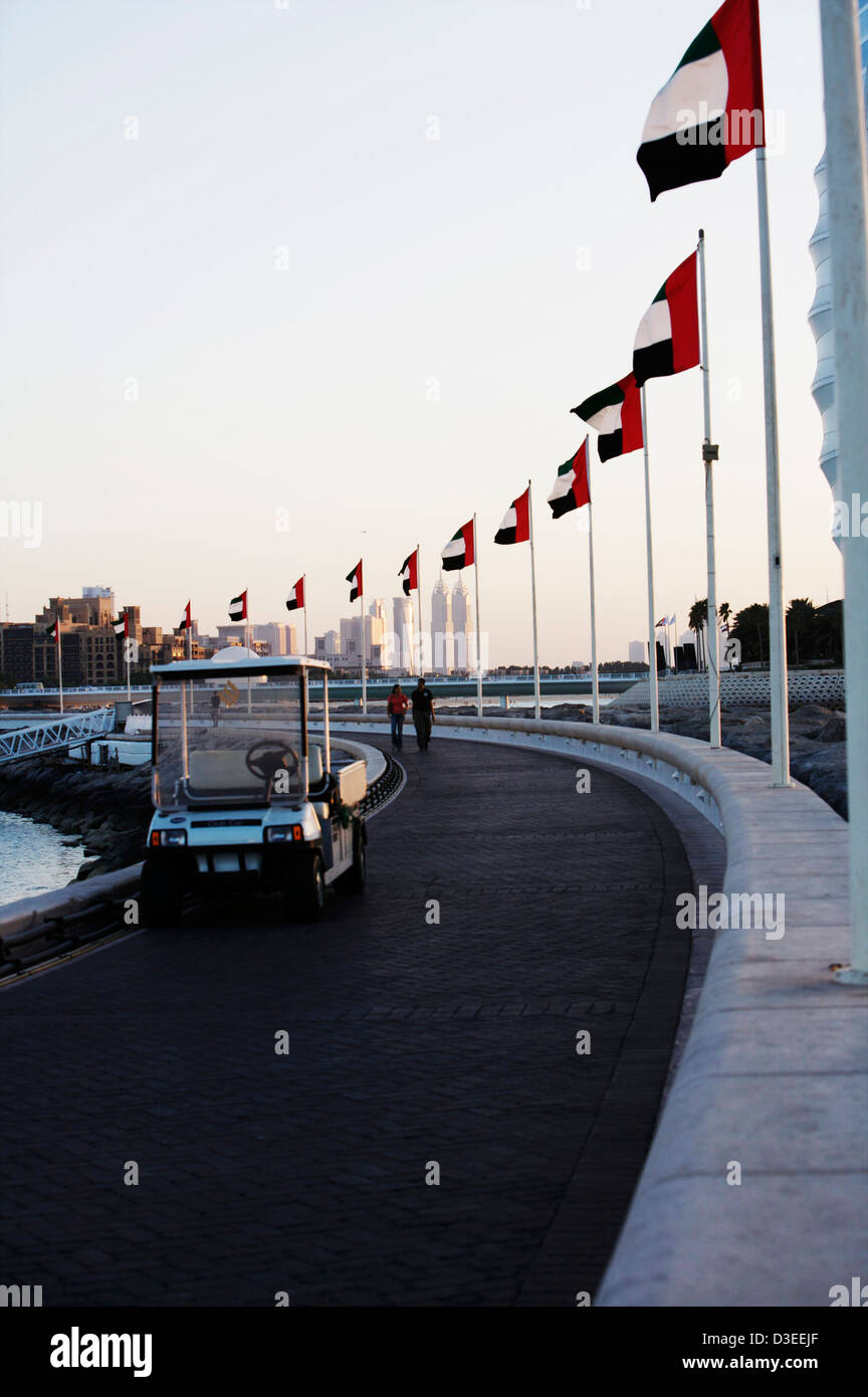 The pier walkway with flags from the Jumeirah Beach Hotel to the Marina seafood restaurant. Walk or take a golf - Stock Image