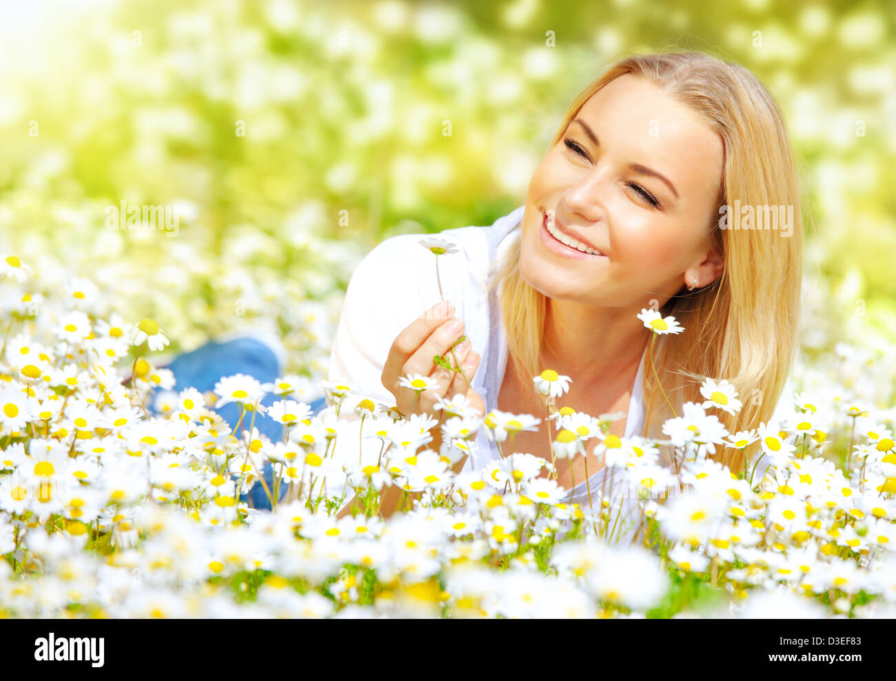Image of sweet girl lying down on daisy glade and enjoying warm sun light, beautiful woman holding in hand little - Stock Image