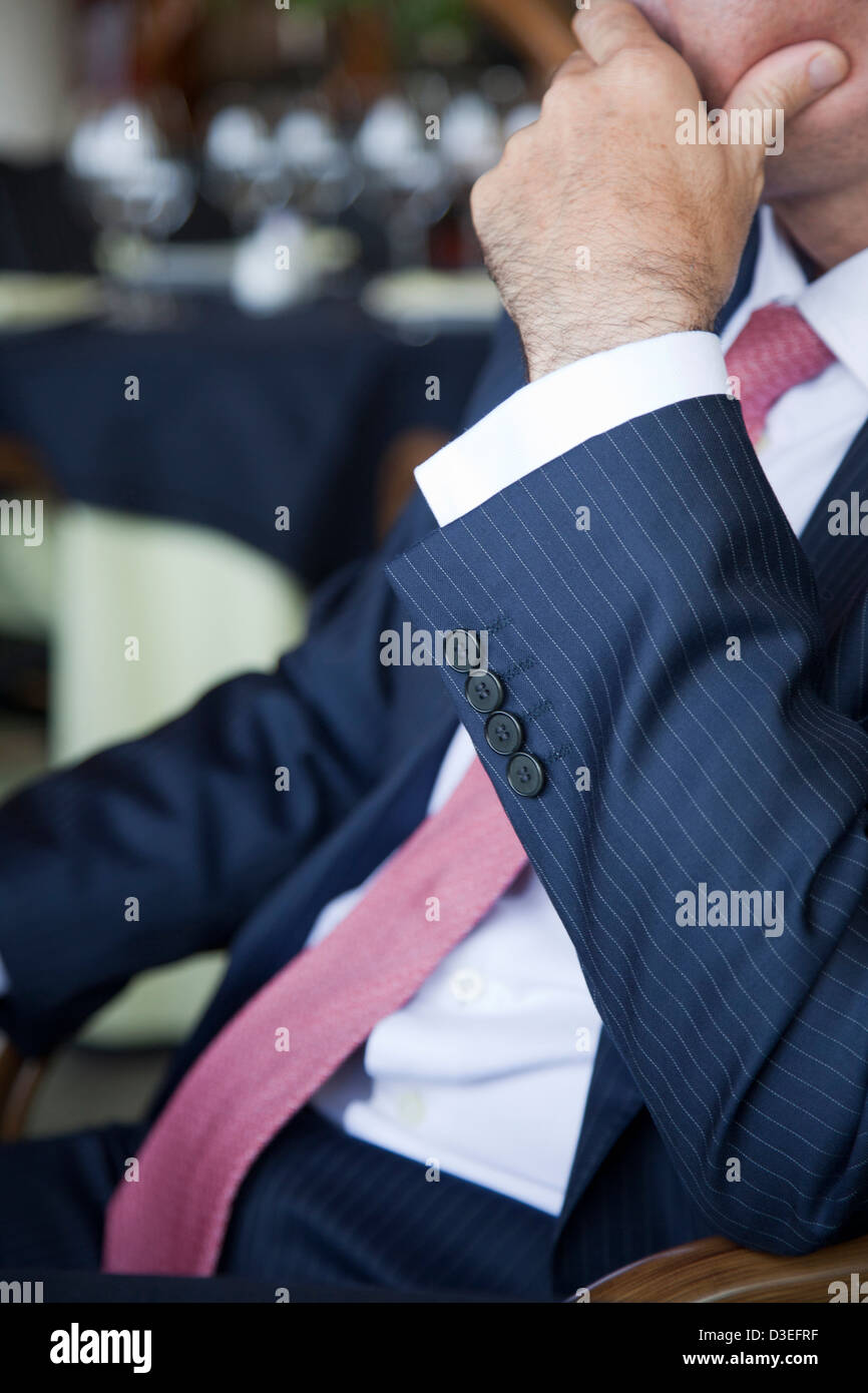 Businessman considering the situation seated a at table in a restaurant during a business lunch. Stock Photo