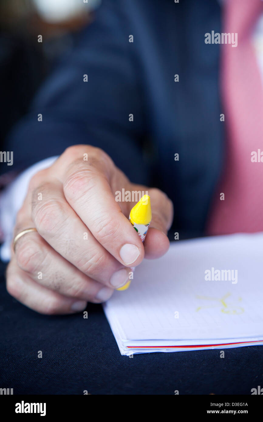 Businessman at at table ready to write with crayons Stock Photo