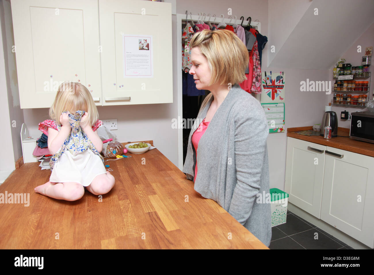 Toddler having a temper tantrum in the kitchen with mum. - Stock Image