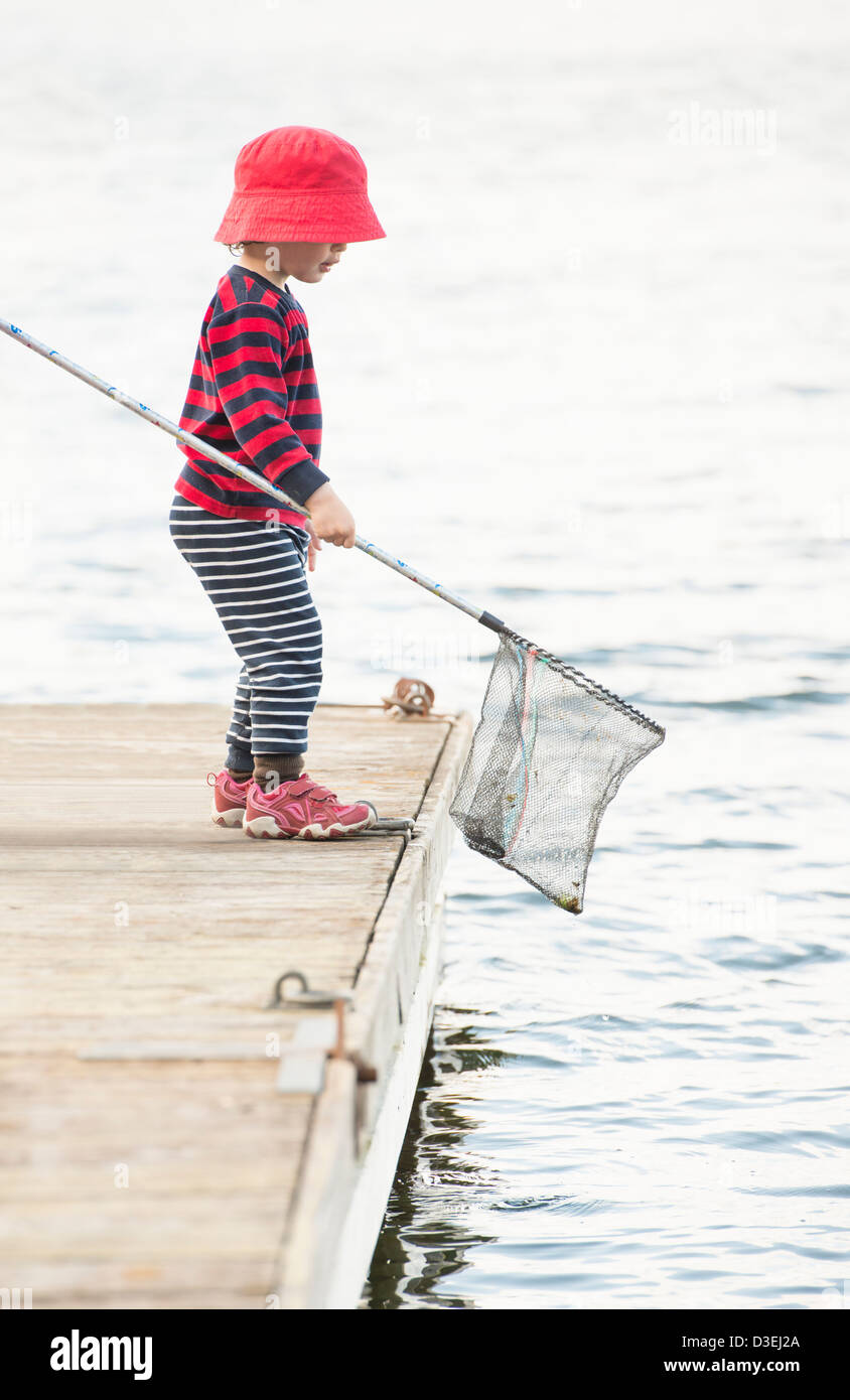 Young child standing on dock by the sea watching the water with fishing net in hand - Stock Image