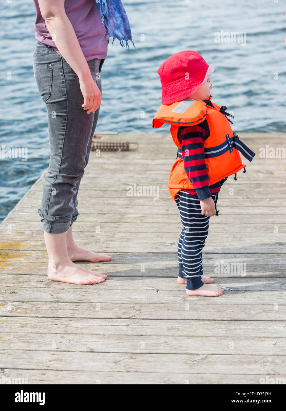 Adult caucasian woman standing barefoot next to her young child on a wooden jetty by the sea Stock Photo