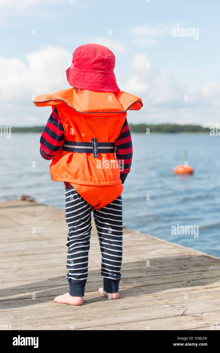 Young child wearing orange life jacket and red hat watching the sea from a wooden jetty - Stock Image